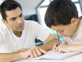 Ein Junge macht mit Hilfe seines Vaters Hausaufgaben