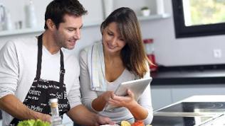 Rezeptsuche (Sujetbild) - Mann und Frau stehen in einer Küche und schauen auf ein Tablet