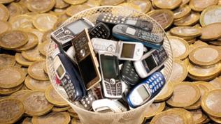 Alte Handys in einem Mülleimer, im Hintergrund liegen viele Münzen