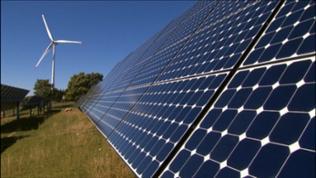 Windrad und Solarmodule auf einer Wiese