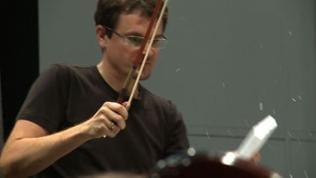 Ein Schlagzeuger hält den Bogen eines Streichinstruments in der rechten Hand und einen weißen Block in der linken.