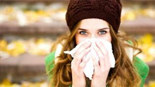 Frau in Mütze und Schal putzt sich die Nase