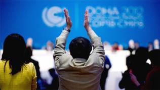 Teilnehmer applaudiert in Doha, Katar, auf der 18. UN-Klimakonferenz bei der Verkündung zur Verlängerung des Kyoto-Protokoll-Abkommens