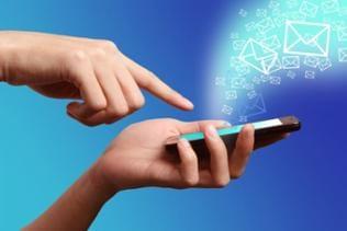 Ein Mann hält ein Smartphone in den Händen, aus dem digital animierte Briefumschläge fliegen.