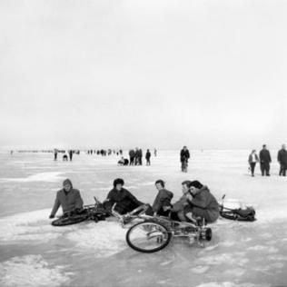 Menschen sitzen mit Fahrrädern auf Eis