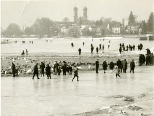 Menschen auf dem gefrorenen Bodensee vor der Schlosskirche Friedrichshafen