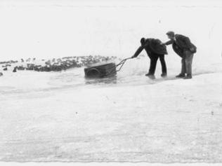 Zwei Männer ziehen einen eingebrochenen Anhänger aus dem Eis