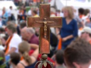 Ein Jesus-Kreuz. Im Hintergrund stehen viele Menschen und unterhalten sich.