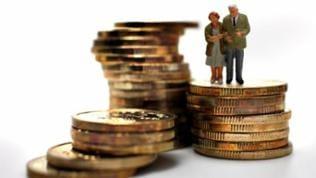 Ein altes Ehepaar (Plastikfiguren) sehen auf aufgestapelten Euromünzen