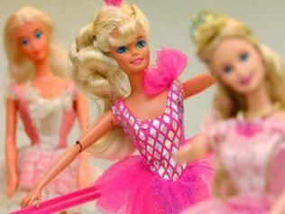 Eine in rosa und silber gekleidete Barbiepuppe mit langen blonden Locken und geschminkten blauen Augen, im Hintergrund verschwommen zwei weitere Puppen