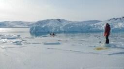Ein Mensch schwimmt im  Eisloch