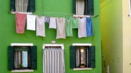 Wäsche auf Wäscheleine vor grünem Haus