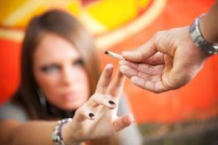 Jugendlicher reicht einer Gleichaltrigen einen Joint.