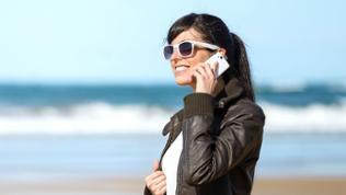 Eine Frau telefoniert mit ihrem Handy am Strand.