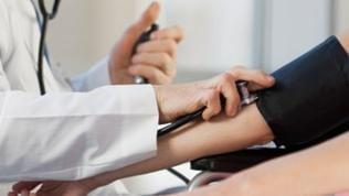 Ein Hausarzt misst den Blutdruck einer Patientin.
