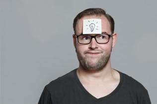Ein Mann hat ein Post-It auf der Stirn mit drei Fragezeichen.