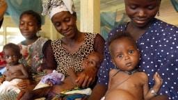 An Malaria erkrankte Kinder sitzen auf den Schößen ihre Mütter.