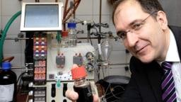 Peter Seeberger zeigt neben der Apparatur zur Herstellung ein Glasgefäß mit einem Fläschchen des Stoffes Artemisinin, das er synthetisch hergestellt hat.