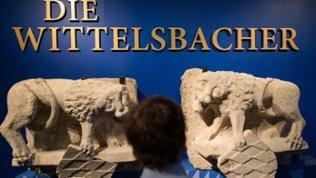 """Zwei Wappen auf Stein mit der Aufschrift: """"Die Wittelsbacher am Rhein"""" im Hintergrund"""