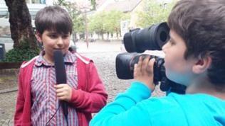 Junge mit Mikrofon wird von einem anderen Jungen mit Kamera gefilmt