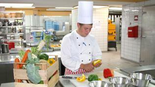 Junger Koch schnippelt Paprika