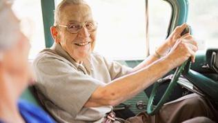 Ein älterer Mann fährt Auto und lächelt seine Beifahrerin an.