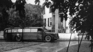 Grauer Bus vor Gebäude
