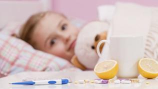 Ein Mädchen liegt krank im Bett. Im Vordergrund stehen Tee, Zitronen und Medikamente.