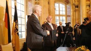 Winfried Kretschmann und Daniel Strauß (Vors. LV dt. Sinti und Roma) unterzeichnen den Staatsvertrag.