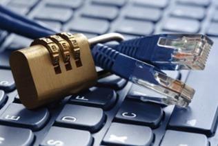 Ein Ethernet-Kabel ist von einem Zahlenschloss umfasst und liegt auf einer Computer-Tastatur.