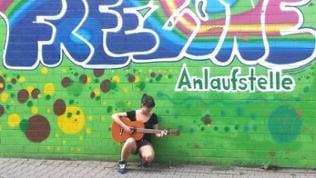 Mädchen spielt Gitarre vor Graffiti