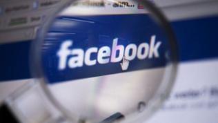 Blick durch eine Lupe auf das Logo des sozialen Netzwerkes Facebook.