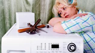 Eine Frau stützt sich neben ihrem Werkzeug auf ihrer Waschmaschine ab.
