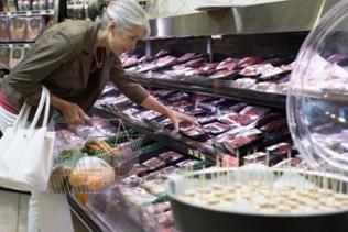 Eine Frau greift nach abgepacktem Hackfleisch in einem Kühlregal in einem Supermarkt.