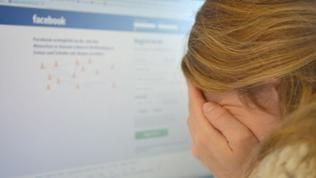 Mädchen verbirgt ihr Gesicht vor Computermonitor