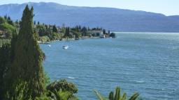 Blick auf See und Häuser, Gärten am See, im Hintergrund Berge