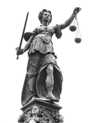Justitia-Statue vor weißem Hintergrund.