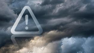 Dunkle Unwetterwolken, auf denen ein Warnschild mit Ausrufezeichen prangt.