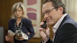 Bürgermeister Faller telefoniert in seinem Büro, im Hintergrund sieht man schemenhaft seine Sekretärin, Frau Heilert