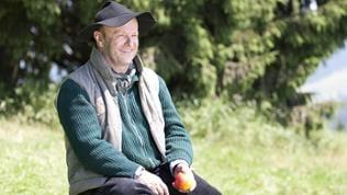 Toni sitzt auf einem Stein und blickt lächelnd in die Gegend