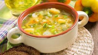 Ein Teller Gemüsesuppe mit Brot.