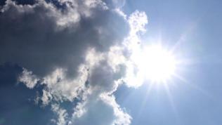 Dunkle Wolken ziehen am Himmel über die Sonne