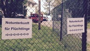 """Maschendrahtzaun mit einem ausgedruckten Schild, auf dem """"Notunterkunft für Flüchtlinge"""" steht"""