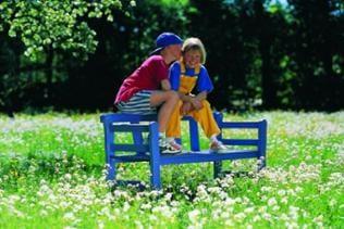 Kinder auf Bank auf Blumenwiese