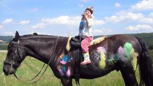 Kleines Mädchen sitzt auf großem Pferd
