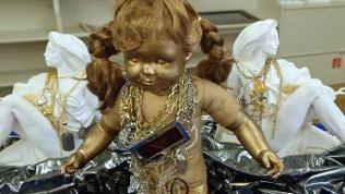 Eine Puppe mit goldfarbenem Gesicht und Zöpfen ist umgeben von zwei weißen Fraunefiguren, alle haben Ketten um den Hals