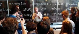 Der Komponist Peter Ablinger steht vor einer Wand mit englischen Wörtern in weißer Schrift und hält einen Vortrag vor Studenten