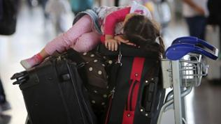 Mädchen schläft auf Koffern auf Trolley im Flughafen