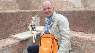 Michael Kost sitzt mit einer Puppe und dem gelben Landesschau Mobil-Rucksack auf einer Treppe.