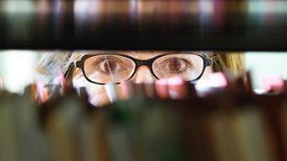 Eine Frau schaut durch ein Bücherregal in einem Archiv hindurch.